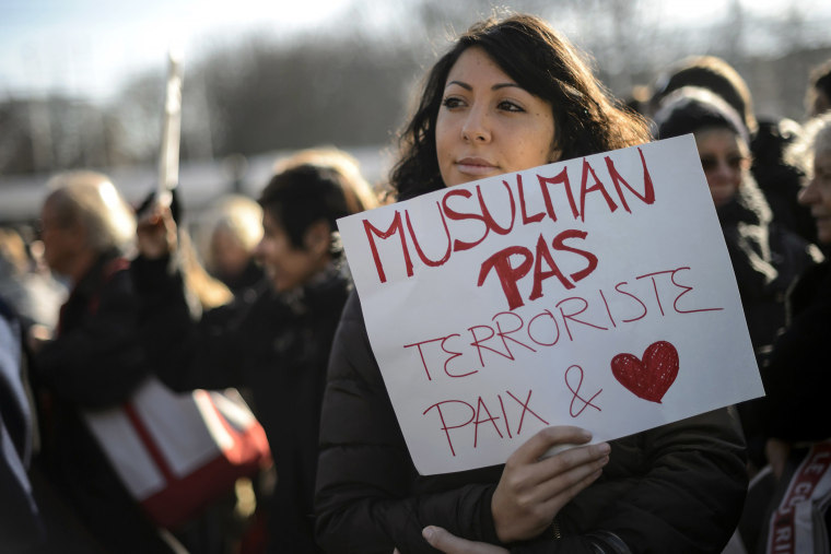 """A woman hold a placard reading in French """"Muslim not terrorists, peace and love"""" during a gathering in the center of Geneva on Jan. 8, 2015 to pay tribute to the twelve people killed the day before in an attack by two armed gunmen on the offices of Fre"""