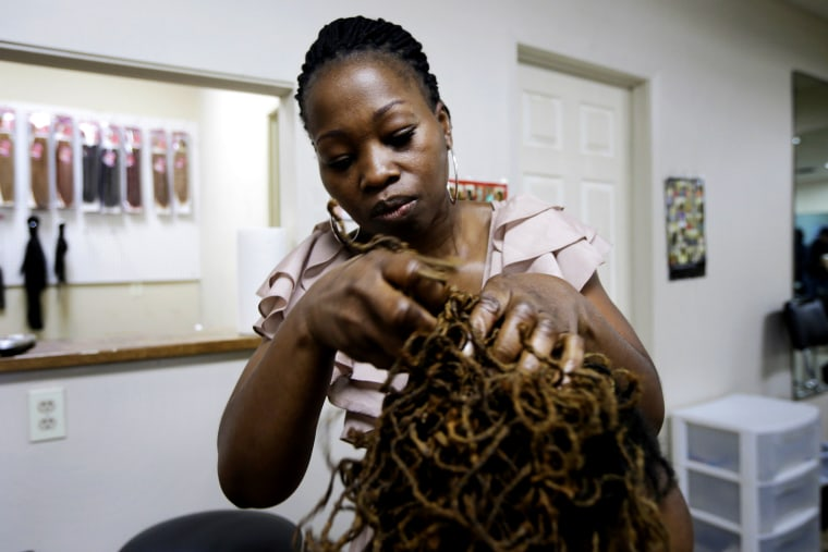 Christine McLean braids a client's hair at her shop in Ark., June 17, 2014 -- one of several states challenging state cosmetology licensing requirements as part of a legal campaign against increased government regulation. (AP Photo/Danny Johnston)