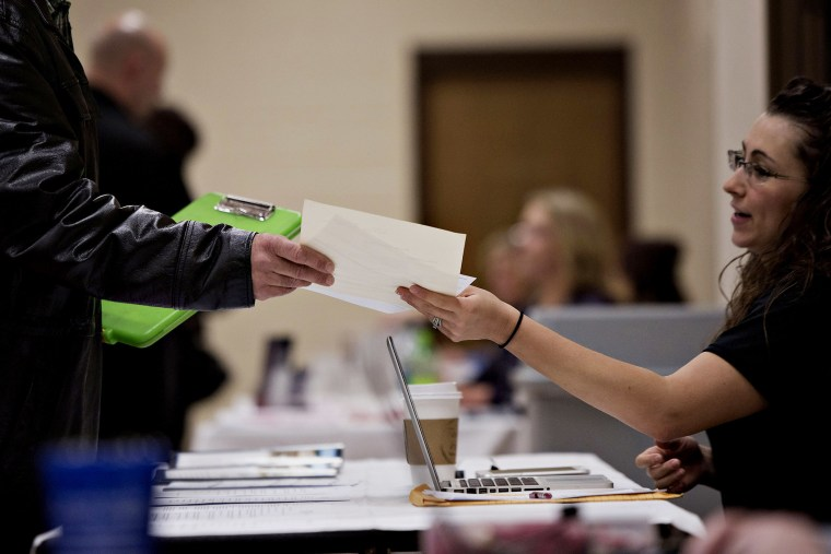 A job seeker talks to a potential employer during a Princeton Area Chamber of Commerce job fair in Princeton, Ill. on Jan. 5, 2015.