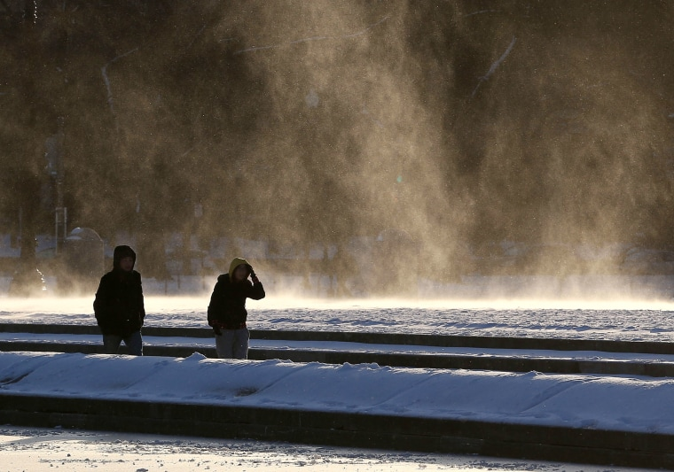 People are windblown as they walk near the frozen reflecting pool in front of the U.S. Capitol on Jan. 7, 2015 in Washington, DC. The Washington area is experiencing heavy winds with temperatures in the teens. (Mark Wilson/Getty Images)