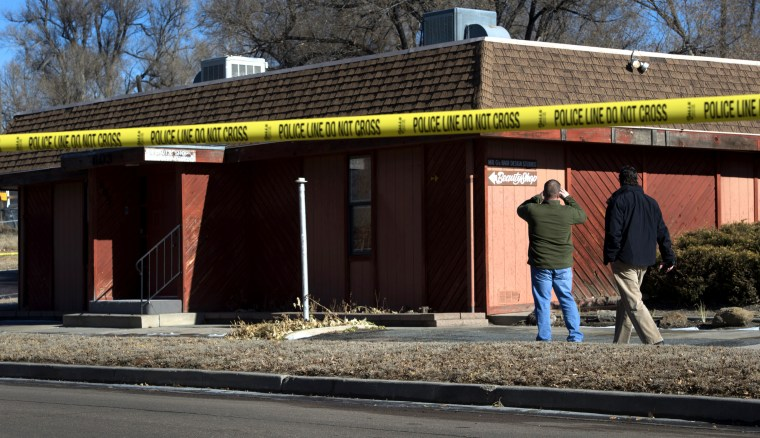 Colorado Springs police officers investigate the scene of an explosion on Jan. 6, 2015, at a building in Colorado, which houses a barber shop and the Colorado Springs chapter of the NAACP. (AP Photo/The Colorado Springs Gazette, Christian Murdock)