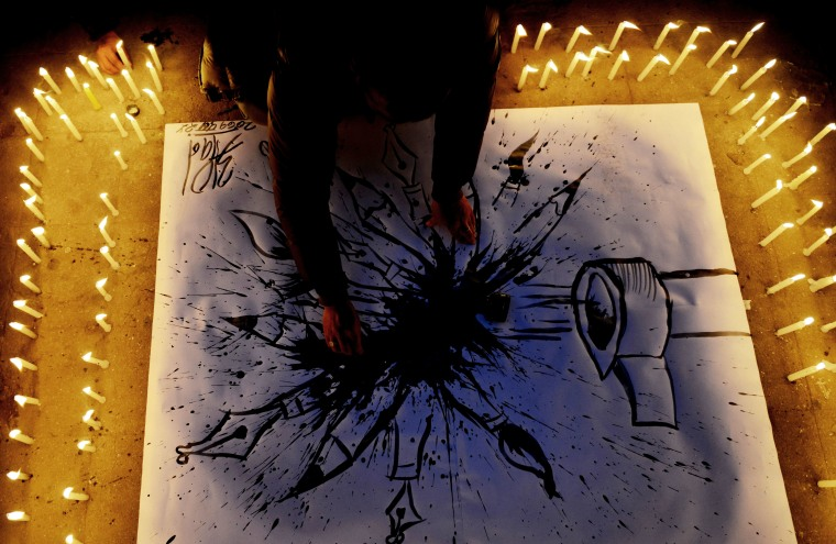 A Nepalese journalist draws a cartoon during a candlelight vigil in solidarity with the victims of an attack by armed gunmen on the offices of French satirical newspaper Charlie Hebdo on Jan. 9, 2015. (PRAKASH MATHEMA/AFP/Getty Images)
