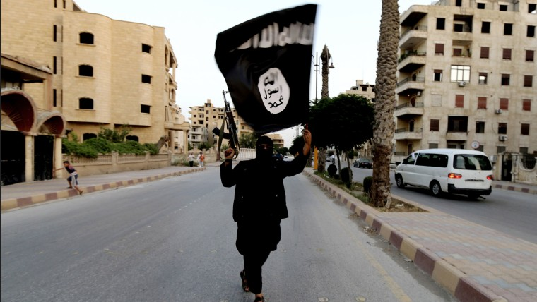 A member loyal to the Islamic State in Iraq and the Levant (ISIL) waves an ISIL flag in Raqqa June 29, 2014. (Photo by Reuters)