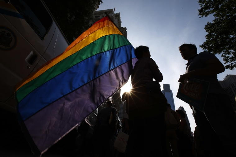 A person holds a gay pride flag during a rally. (Photo by Matt Slocum/AP)