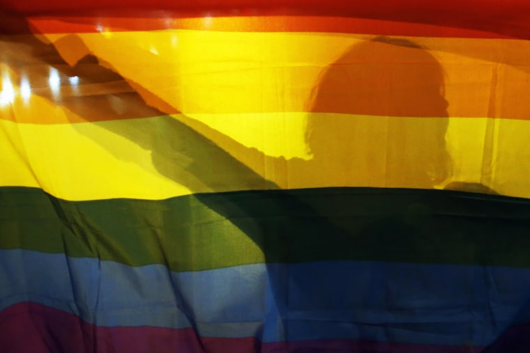 A gay rights activist holds a rainbow flag. (Photo by Marko Djurica/Reuters)
