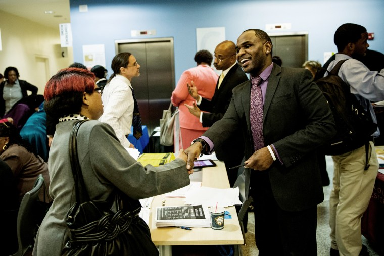 Carl Gilbert (R), of Upper Manhattan Work Force 1 Career Center, meets with a woman looking for a job at a jobs fair at the Bronx Public Library on Sept. 17, 2014 in the Bronx Borough of New York, N.Y. (Photo by Andrew Burton/Getty)