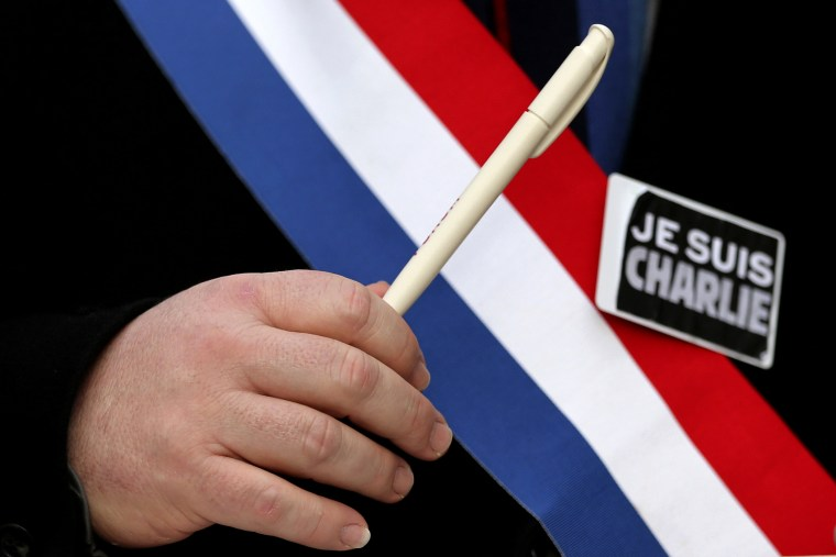 "A man holds a pen and wears a sticker reading ""Je suis Charlie"" during a march for the victims of the shootings by gunmen at the offices of the satirical weekly newspaper Charlie Hebdo in Paris, in Brussels"