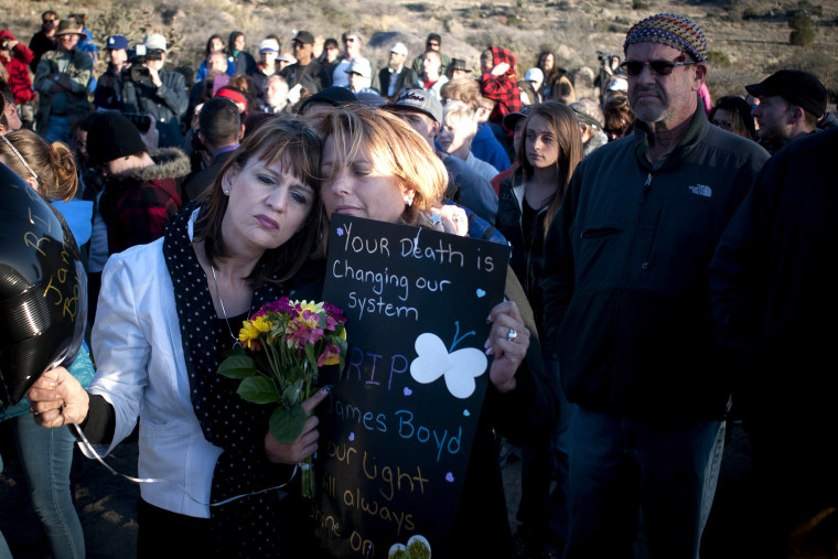 Star Garrett, left, and Shannon Haley, second from left, embrace during the vigil for James Boyd Albuquerque on April 2, 2014.