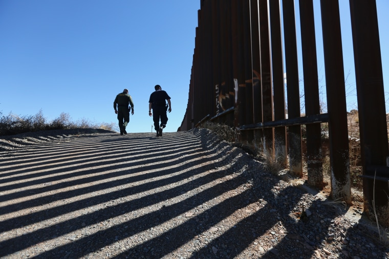 U.S. Customs and Border Protection personnel walk along a section of the recently-constructed fence at the U.S.-Mexico border on Feb. 26, 2013 in Nogales, Ariz. (Photo by John Moore/Getty)