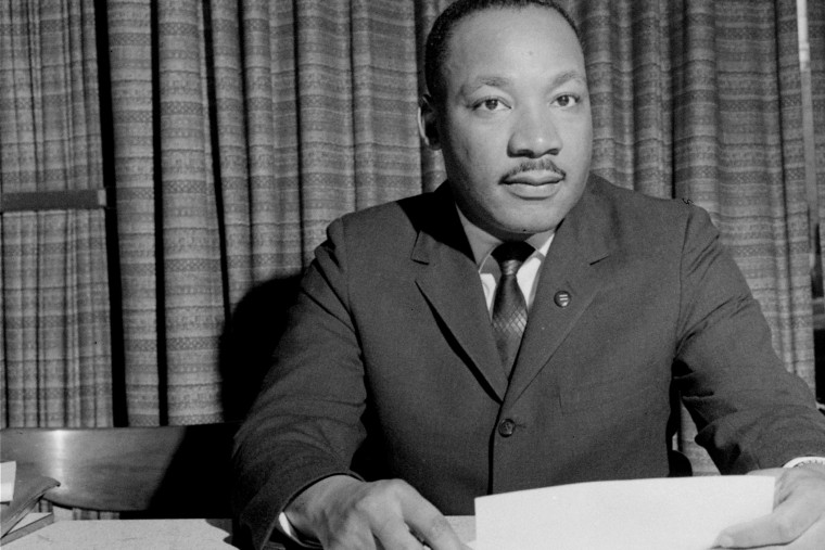 Dr. Martin Luther King, Jr. is shown discussing a forthcoming speech, March 18, 1964, from his home in Atlanta, Ga. (Photo by AP)