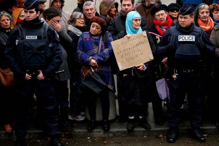 Amid tight security, a woman holds up a sign saying 'I am a Muslim. I come to share your grief' as members of the public pay respects at the funeral of Charlie Hebdo a cartoonist on Jan. 15, 2015 in Paris, France.  (Photo by Christopher Furlong/Getty)