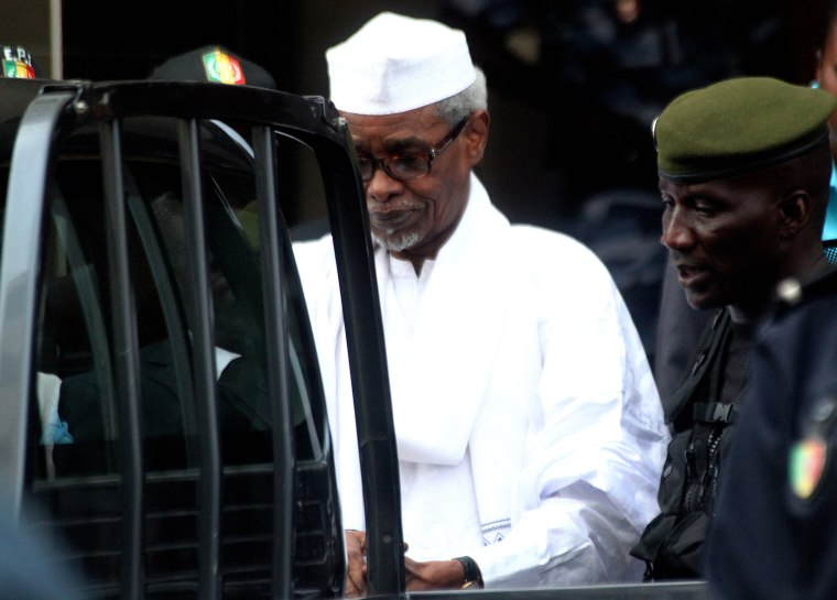Former Chadian dictator Hissene Habre, charged with genocide, war crimes, torture and crimes against humanity, is escorted by military officers after being heard by judge on July 2, 2013 in Dakar. (Photo by STRINGER/AFP/Getty)