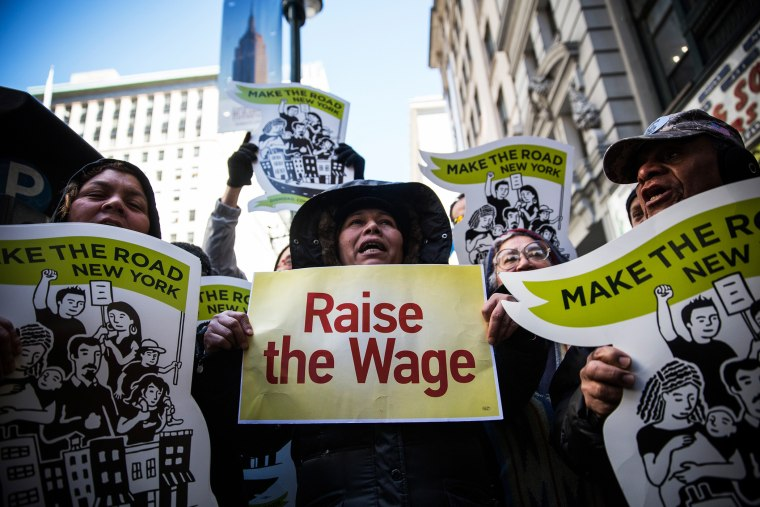 Women hold banners during a protest for higher wages for fast food workers on March 18, 2014 in New York, N.Y. (Photo by Andrew Burton/Getty)