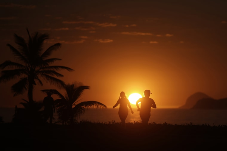 People exercise in Barra da Tijuca beach during the sunrise in Rio de Janeiro (Photo by Ricardo Moraes/Reuters)