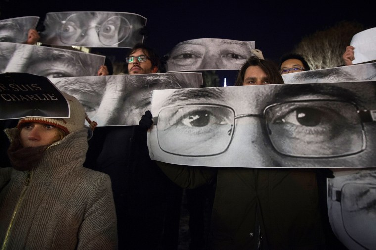 People hold up posters with the eyes of Charlie Hebdo Editor Stephane Charbonnier (front) and Jean Cabut (back L) during a vigil to pay tribute to the victims of the Paris shooting, in the New York City Jan. 7, 2015. (Photo by Carlo Allegri/Reuters)
