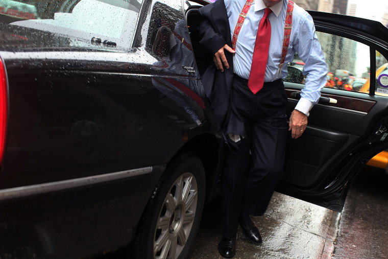 A business man gets out of a town car in New York City. (Photo by Spencer Platt/Getty)