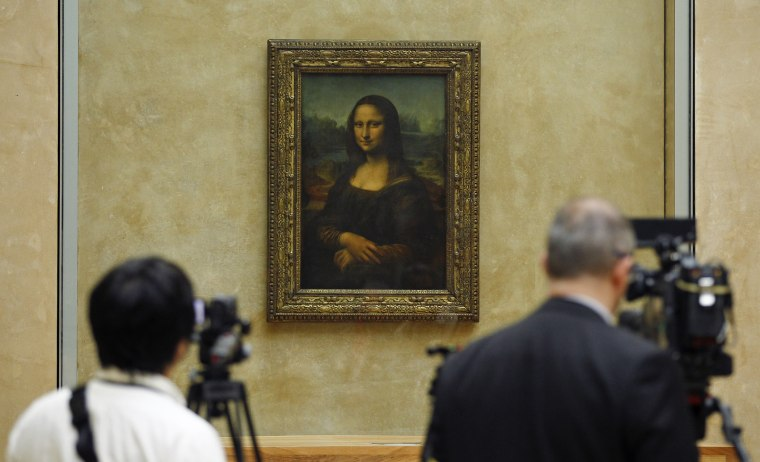Members of the media are gathered next to the Mona Lisa, during an event to unveil the new lighting of Leonardo da Vinci's painting Mona Lisa, also known as La Joconde, at the Louvre museum in Paris, Tuesday June 4, 2013.