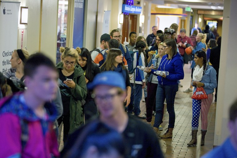 People wait in line to vote at busy polling facility on the Auraria Campus in Denver, Colo.