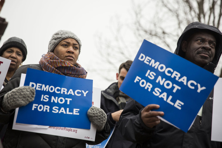 Attendees hold signs during a rally calling for an end to corporate money in politics and to mark the fifth anniversary of the Supreme Court's Citizens United decision on Jan. 21, 2015 in Washington, D.C. (Photo by Drew Angerer/Getty)