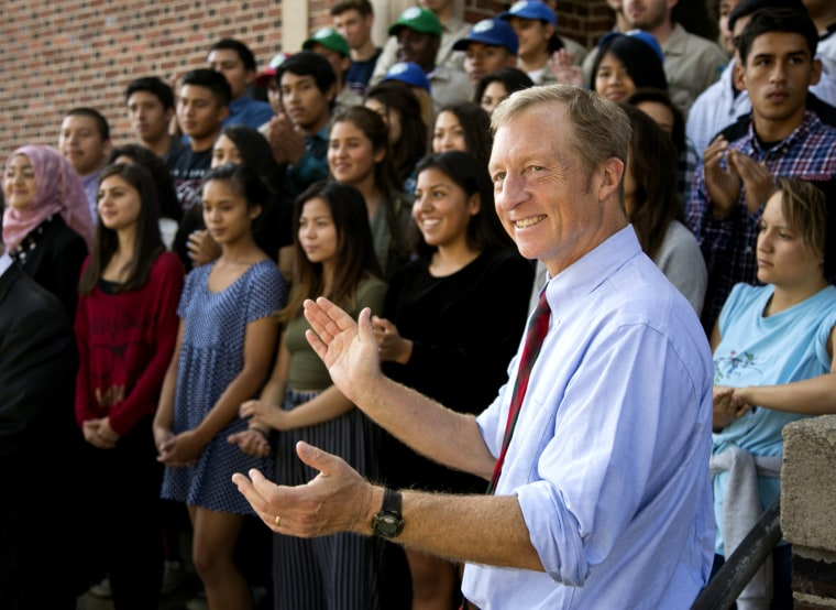 California Prop. 39 co-chair Tom Steyer takes photos with students at John Marshall High School in Los Angeles, Oct. 28, 2014. (Photo by Damian Dovarganes/AP)