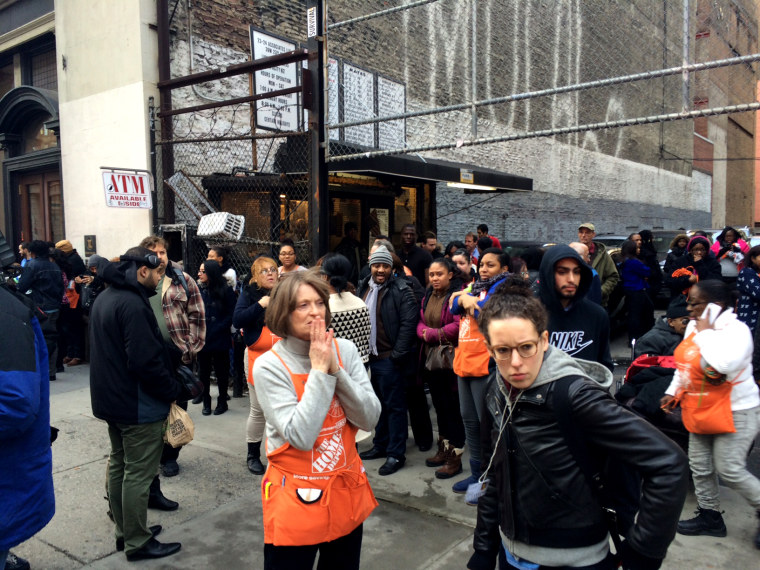 Home Depot employees and customers stand outside a store after shots were fired in a Chelsea, New York City location on Jan. 25, 2015. (Photo by David Hashim/MSNBC)