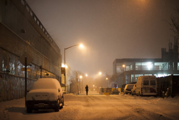 A woman walks down a street at night during snowfall in north Brooklyn, N.Y. on Jan 26, 2015.