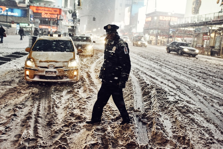 A taxi dispatcher on 7th Ave near Penn Station as commuters try to get home before the approaching storm on Jan. 26, 2015.