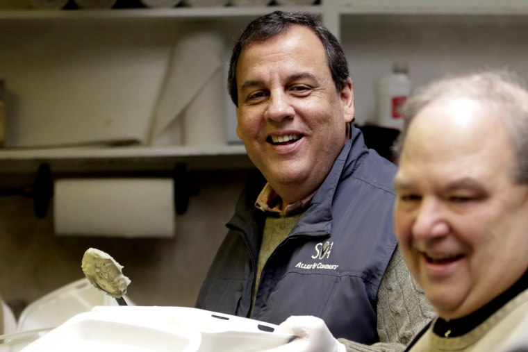 New Jersey Gov. Chris Christie, left, and Newark Archbishop Bernard Hebda converse while preparing plates to hand out during a pre-Thanksgiving meal at the St. John's Church soup kitchen on Nov. 26, 2014, in Newark, N.J.