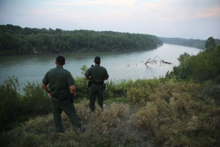 U.S. Border Patrol agents look for immigrants crossing the Rio Grande from Mexico (L), to the United States at dusk on July 24, 2014 near Mission, Texas. (Photo by John Moore/Getty)