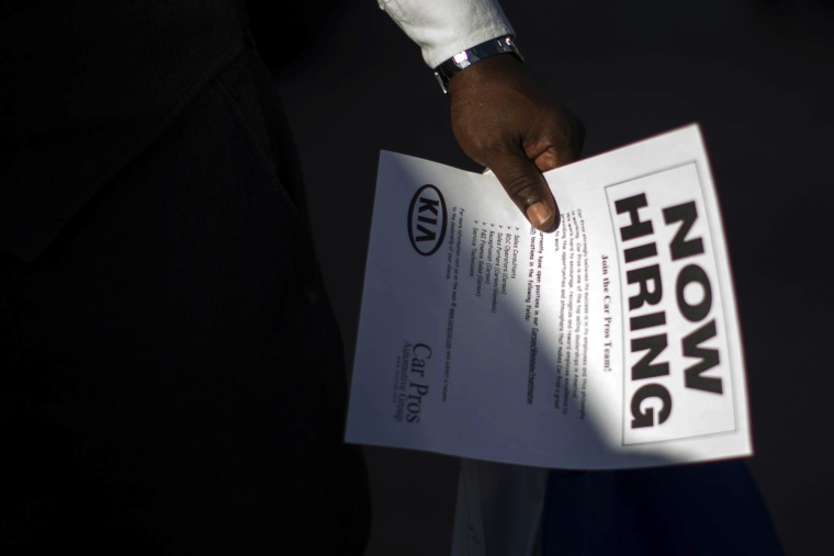 A man holds a leaflet at ' job fair in Carson, Calif. on Oct. 3, 2014