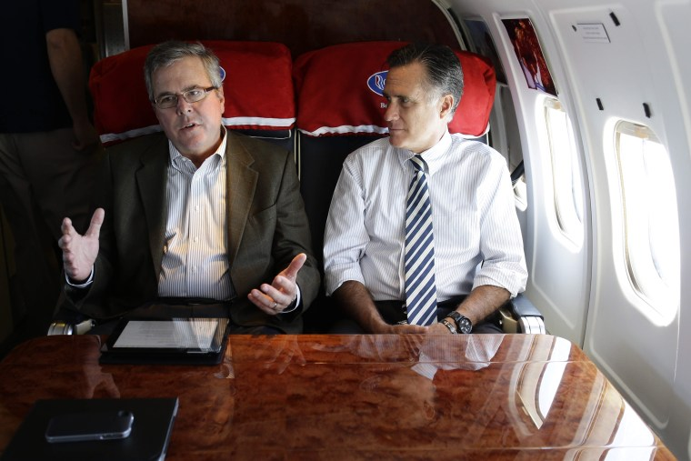 Republican presidential candidate, former Massachusetts Gov. Mitt Romney talks with former Florida Gov. Jeb Bush as they fly on his campaign plane to Miami Fla., Oct. 31, 2012. (Photo by Charles Dharapak/AP)