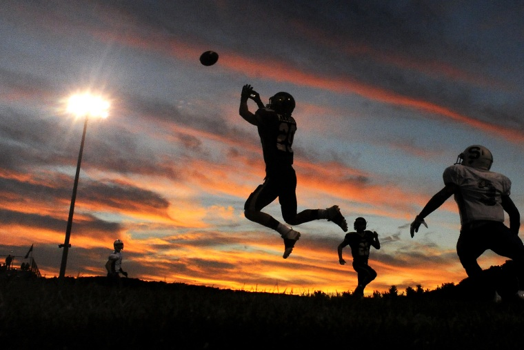 A player jumps to intercept a pass during a high school football game. (Photo by Jimmy May/Bloomsburg Press Enterprise/AP)