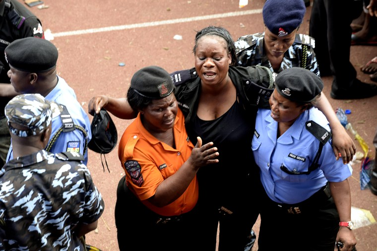 Policewomen help a colleague injured during fracas that broke out during a presidential campaign rally of Nigeria's main opposition All Progressives Congress (APC) at Taslim Balogun Stadium in Lagos on Jan. 30, 2015. (Photo by Pius Utomi Ekpei/AFP/Getty)