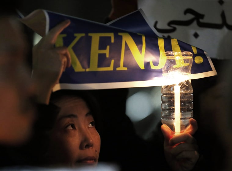 A woman holding a candle and placard takes part in a vigil in front of Prime Minister Shinzo Abe's official residence in Tokyo, Jan. 30, 2015. (Photo by Toru Hanai/Reuters)