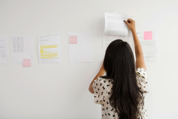 A Businesswoman tapes up papers on an office wall. (Photo by Gallery Stock)