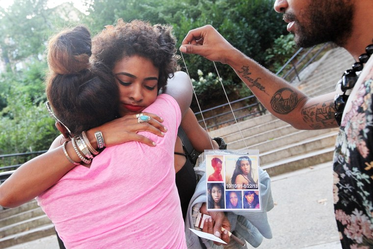 Dejia Ferguson (C), a friend of slain transgender woman Islan Nettles, hugs another mourner before a vigil for her as a man holds photos of Nettles at Jackie Robinson Park in Harlem on Aug. 27, 2013 in New York City.
