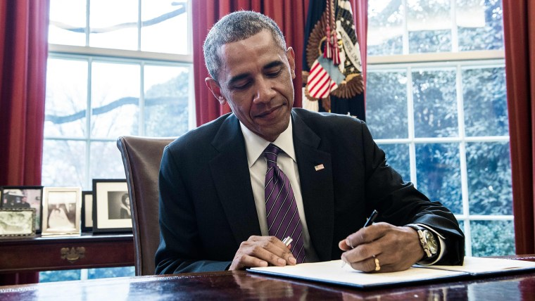 President Barack Obama signs a presidential memorandum in the Oval Office of the White House in Washington, D.C., on Jan. 15, 2015. (Photo by Nicholas Kamm/AFP/Getty)