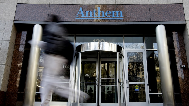 A pedestrian walks past the corporate headquarters of health insurer Anthem, formerly known as Wellpoint, on Dec. 3, 2014 in Indianapolis. (Photo by Darron Cummings/AP)
