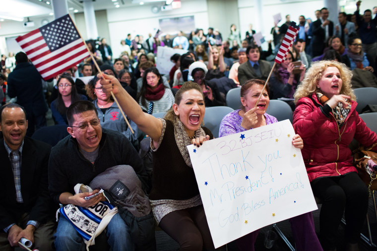 Lilian Aguayo (L), Fadila Mrkulic and Tatiana Lambert hold signs and wave flags during a viewing party for resident Barack Obama's speech on executive action immigration policy reform on Nov. 20, 2014 in New York, N.Y. (Photo by Kevin Hagen/Getty)