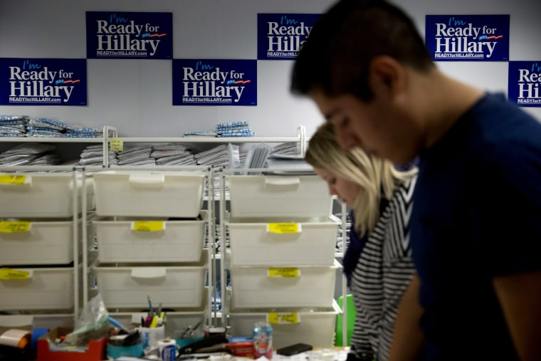 """""""I'm Ready for Hillary"""" posters hang on the wall as interns fulfill customer's orders at the Ready For Hillary PAC headquarters store in Arlington, Virginia, on Nov. 12, 2014. (Photo by Andrew Harrer/Bloomberg via Getty)"""