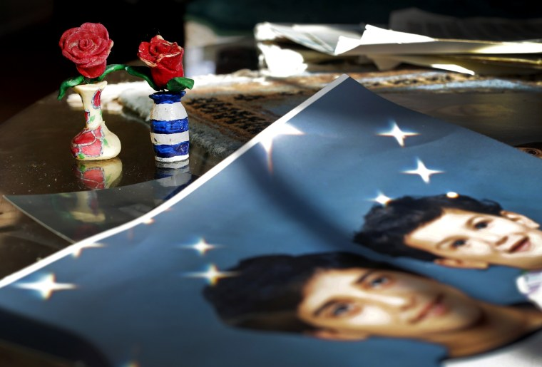 In this Dec. 10, 2014 photo, Prison artwork created by Adnan Syed sits near family photos in the home of his mother, Shamim Syed, in Baltimore, Md. (Photo by Patrick Semansky/AP)