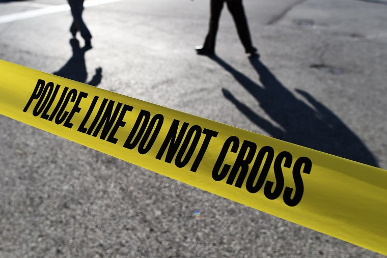 Police officers stand behind crime scene tape. (Photo by Jewel Samad/AFP/Getty)