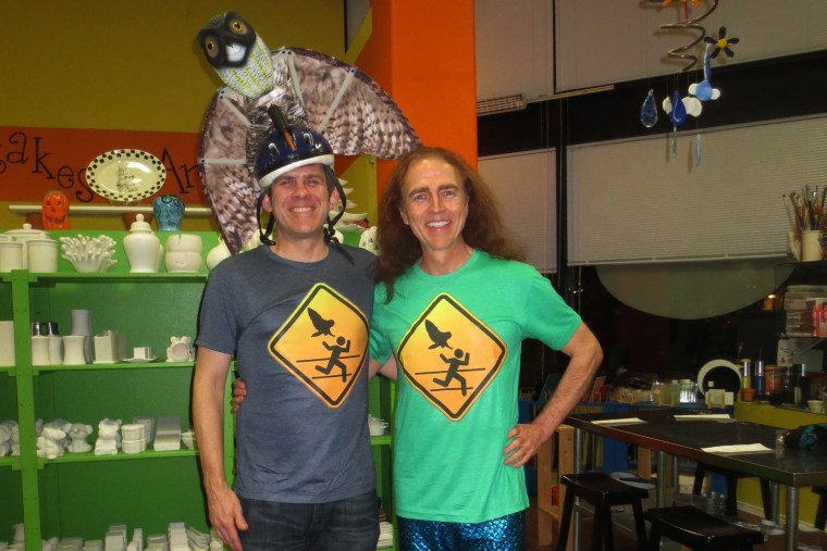 Dr. Ron Jaecks, owl attack-surviving jogger, poses with a homemade owl warning sign t-shirt.