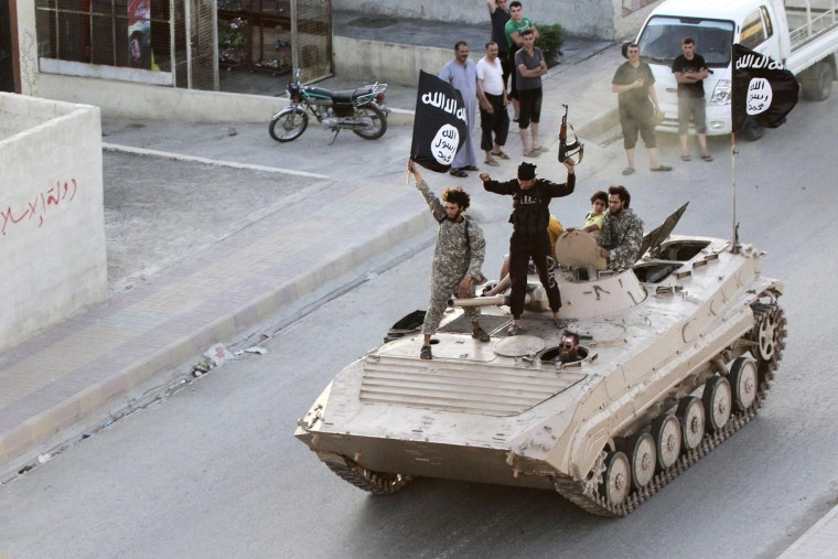 Militant Islamist fighters take part in a military parade along the streets of northern Raqqa province on June 30, 2014.