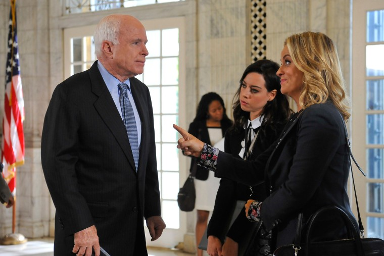 """Senator John McCain, Aubrey Plaza as April Ludgate and Amy Poehler as Leslie Knope are seen in the episode """"Ms. Ludgate-Dwyer Goes to Washington"""" from the show Parks and Recreation. (Photo by Larry French/NBC/NBCU Photo Bank/Getty)"""