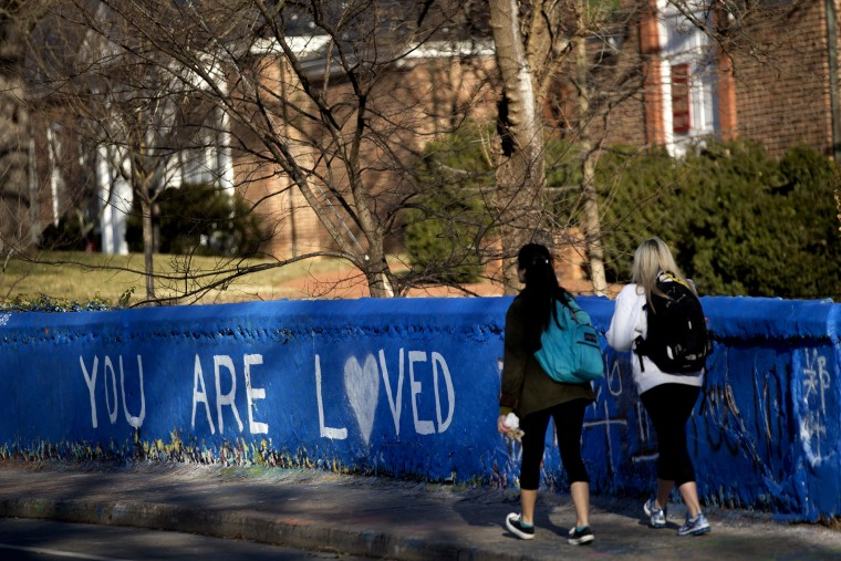 """Students walk past the message \""""You are Loved\"""" painted on a wall next to the Beta Bridge near the University of Virginia campus in Charlottesville, Va. on Jan. 16, 2015."""