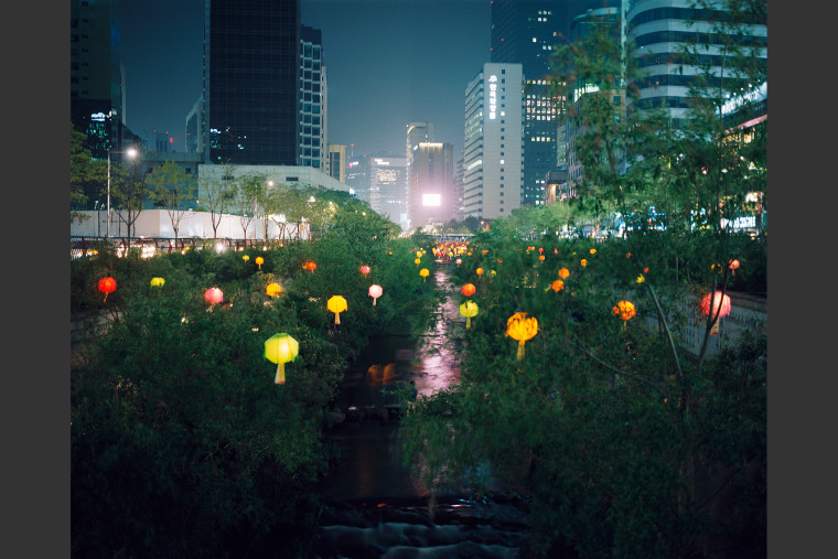 Buddhist lanterns line a public garden in Seoul celebrating the Buddha's birthday. That morning the author met Mrs. Shin Kyung Hee who gave up her infant...