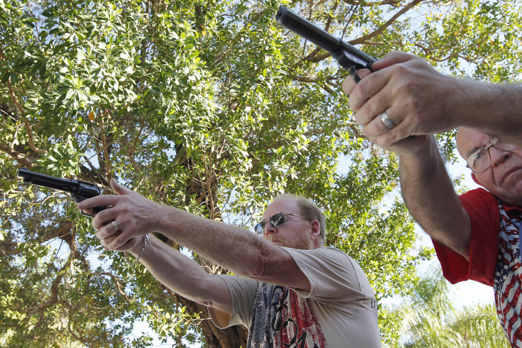 Varrieur and Gordon practice their firing stance with unloaded weapons in the yard of Varrieur's home in Big Pine Keys. (Photo by Andrew Innerarity/Reuters)