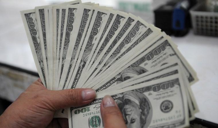 An employee at a money changer counts $100 bills.