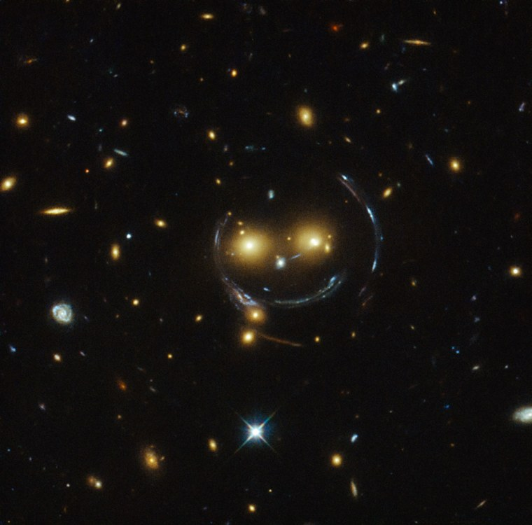 """In the case of this \""""€œhappy face,\"""" the two eyes are the galaxies SDSSCGB 8842.3 and SDSSCGB 8842.4 and the misleading smile lines are actually arcs caused by an effect known as strong gravitational lensing. February 9, 2015"""
